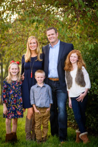 Dr. Ries' wife, two daughters and son standing outside in front of a tree.