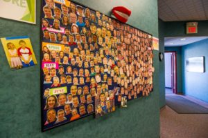 Bulletin board on a dark green wall with before and after photos attached to it.