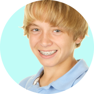 Young teen boy smiling with brown hair and braces in a blue shirt infront of a teal green background.