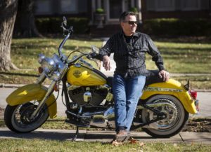 Orthodontist, Dr. Robinson sitting on a yellow motorcycle.