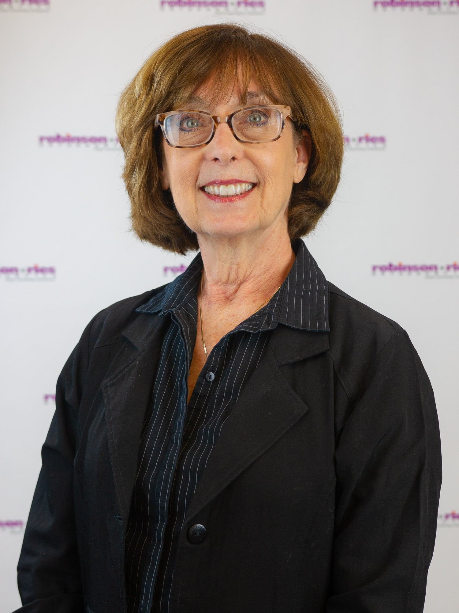 Denise, in a black and grey long sleeve shirt with a white background.